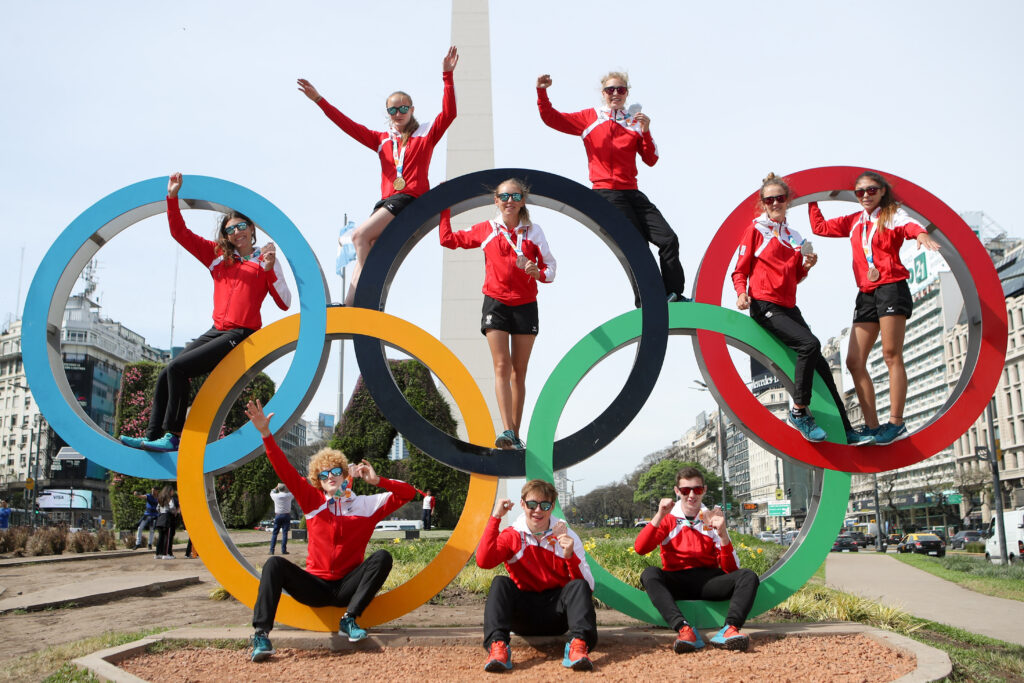 Sportler sitzten auf einer Skulptur der olympischen Ringe