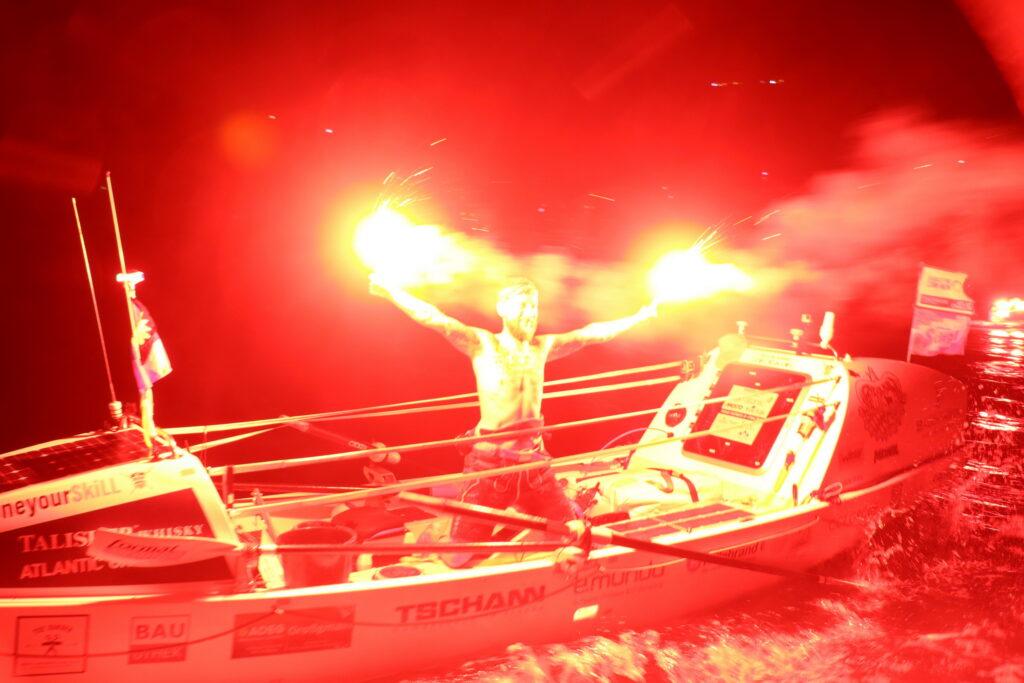 Mann auf einem Boot mit roten Fackeln in den Händen