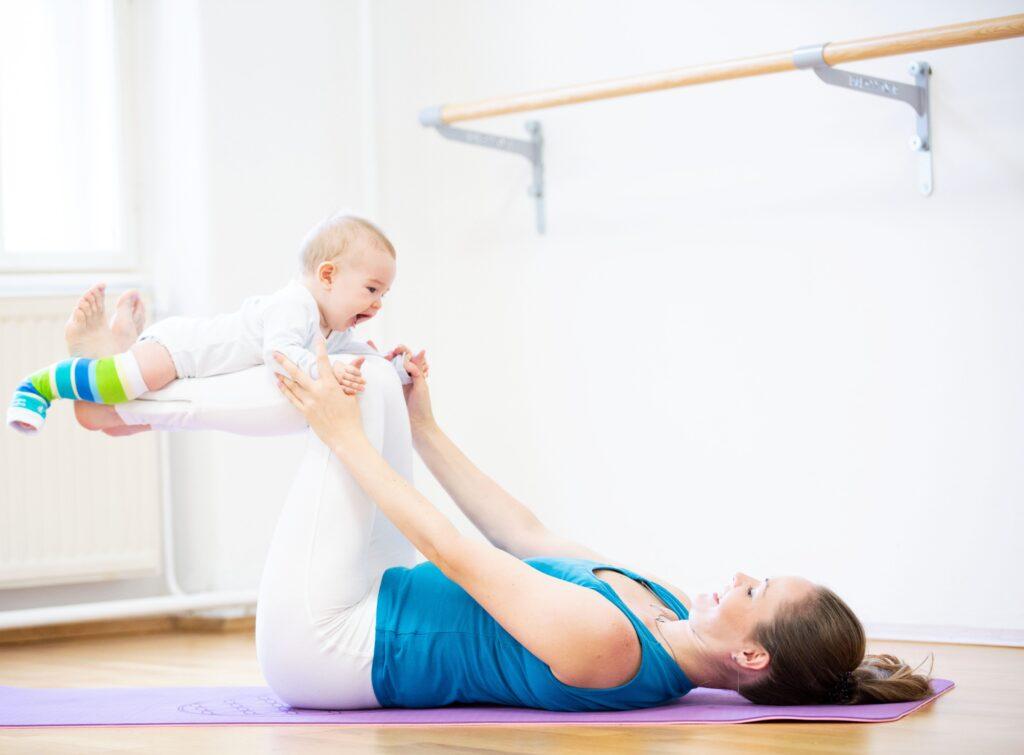 Frau turnt mit Baby
