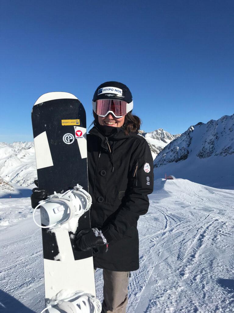 Pia Zerkhold steht mit ihrem Snowboard auf. einer Pist