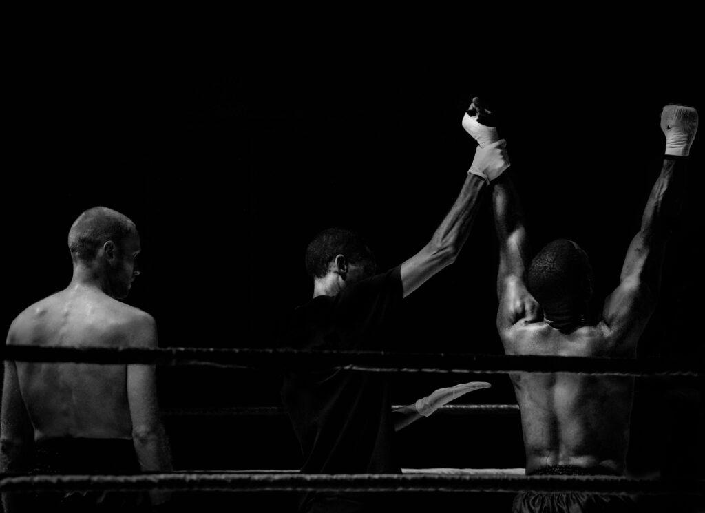 Zwei Boxer und ein Ringrichter, der den Arm des SIegers hochhebt.