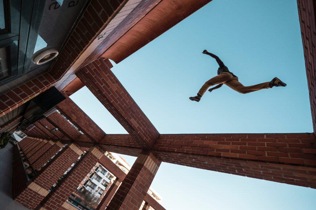 Eine Person springt über eine Mauer