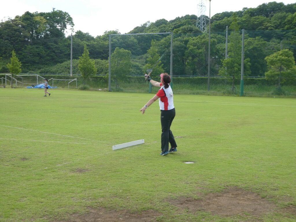 Eine Frau wirft auf. einem Sportplatz ihre Angel aus