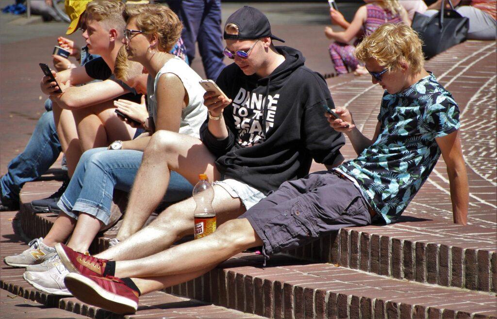 Junge Menschen sitzten und betrachten ihr Handy