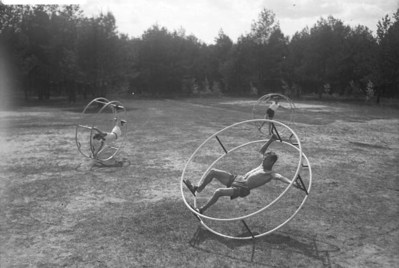 Altes Bild mit drei Sportlern auf ihren Rhönrädern