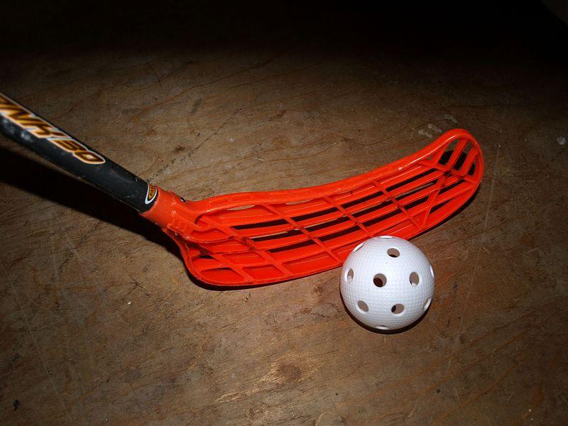 Ein roter Floorballschläger mit einem weißen Ball