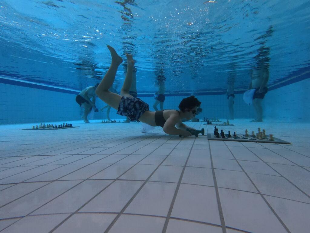 Unterwasserschachspielerin macht einen Zug