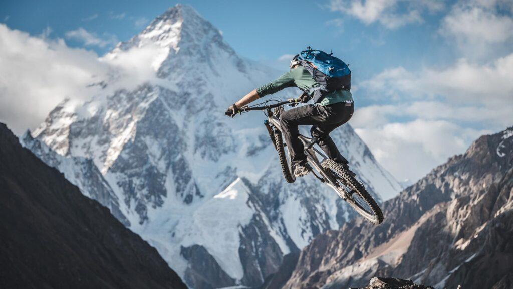 Ein Mountainbiker springt mit seinem Rad vor der Kulisse des K2