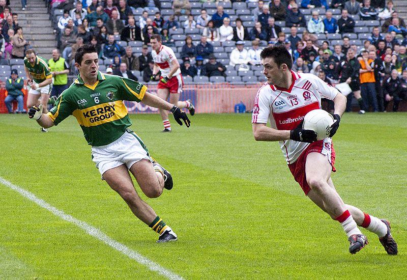 Zwei Gaelic Footballspieler laufen mit dem Ball