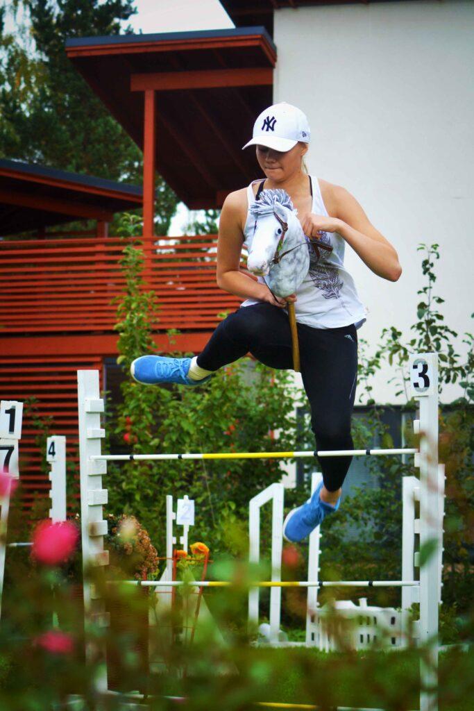 Mädchen hüpft mit dem Steckenpferd über ein Hindernis