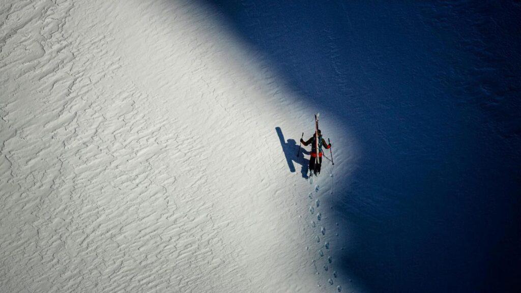 Ein Skifahrer marschiert mit seinen Skiern am Rücken einen Schneehang hinauf