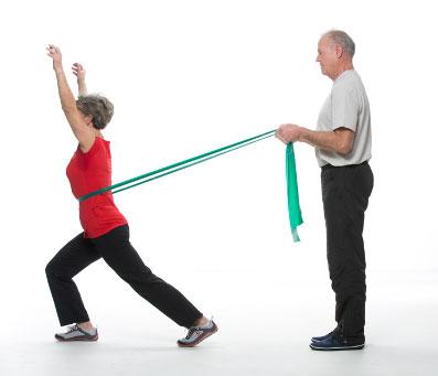 Ein älteres Paar führt eine Wirbelsäulenübung durch